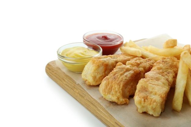Bordo con pesce fritto e patatine fritte e salse isolate su bianco