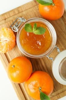 Bordo con marmellata di mandarini e ingredienti su sfondo bianco