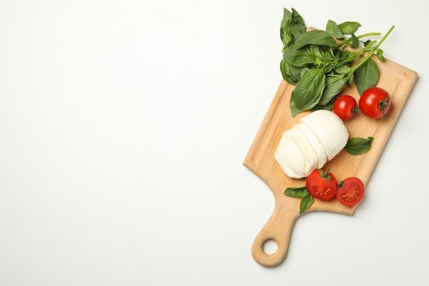 Consiglio con mozzarella, pomodoro e basilico su sfondo bianco