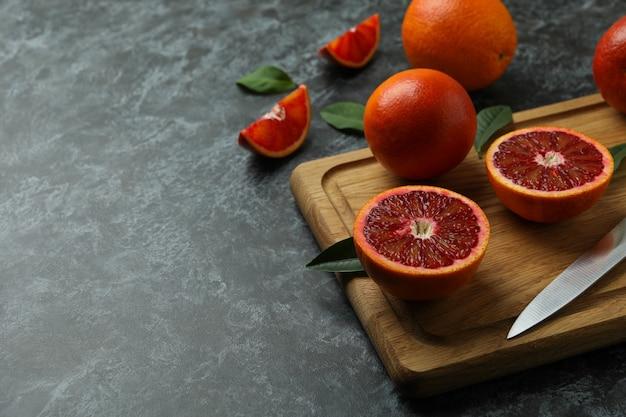 Bordo con arance rosse, foglie e coltello sul tavolo fumoso nero