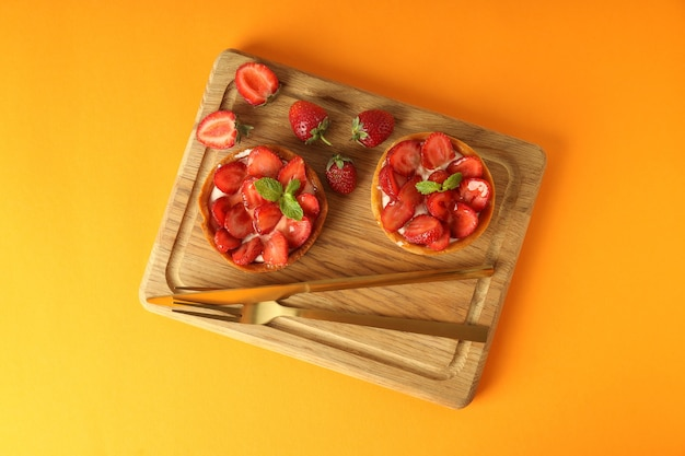 Bordo con crostate di fragole su sfondo arancione.