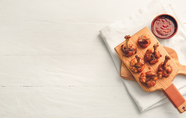 Consiglio con gustosi lecca-lecca di pollo e salsa su una superficie in legno chiaro