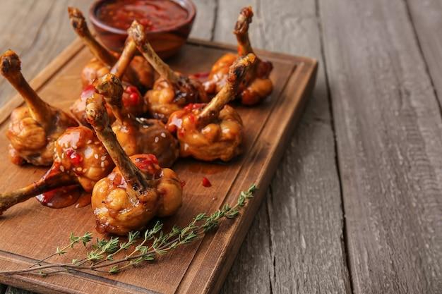 Pensione con gustosi lecca-lecca di pollo su una superficie di legno