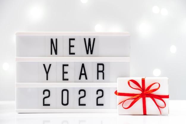 Bordo con testo e confezione regalo sullo sfondo bokeh di fondo. anno nuovo concetto 2021.