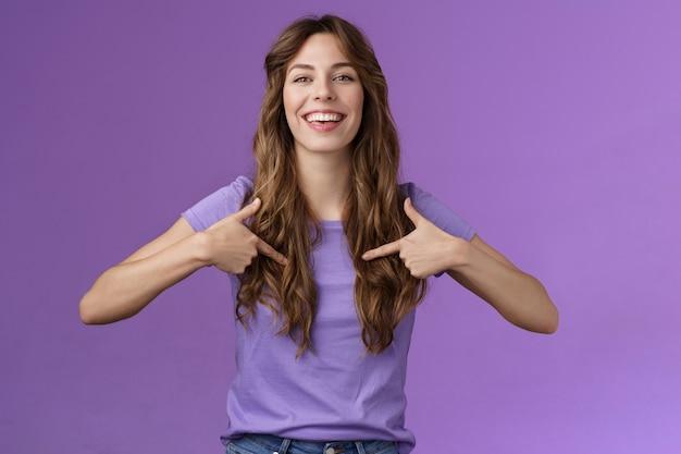 Una bella femmina europea riccia che si vanta che si indica orgogliosa di chi sta sorridendo felice che esce il mese dell'orgoglio sorridente che indica ampiamente il centro del petto che si vanta di sfondo viola