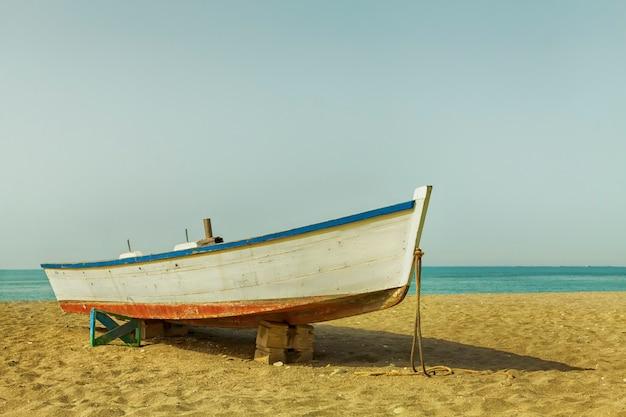 Barca sulla spiaggia skyline una piccola barca di legno usata dai pescatori spiaggiata sulla spiaggia di sabbia vicino al mar mediterraneo Foto Premium