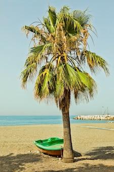 Barca sulla spiaggia skyline una piccola barca di legno usata dai pescatori spiaggiata sulla spiaggia di sabbia vicino al mar mediterraneo