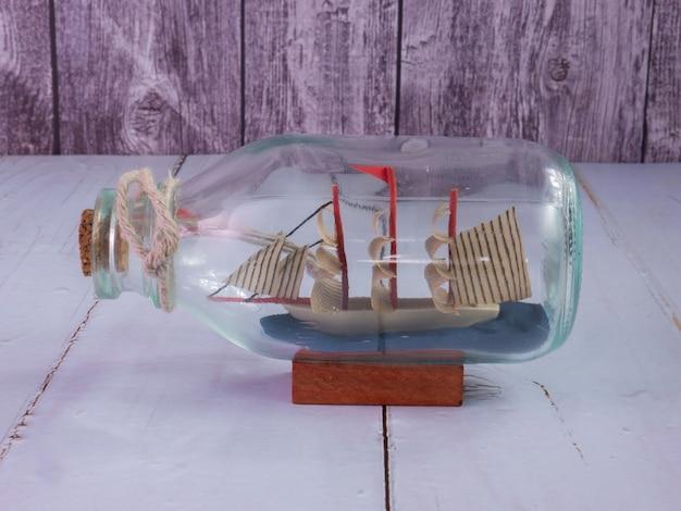 La barca in bottiglia sul tavolo di legno per il concetto di viaggio o di trasporto