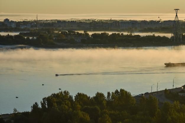 La barca galleggia sul fiume attraverso la nebbia