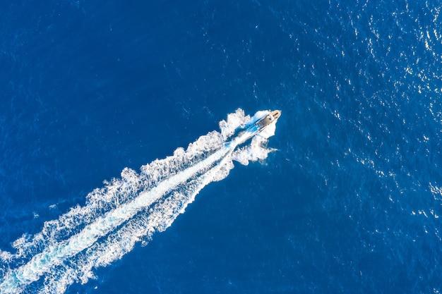 Il lancio della barca ad alta velocità galleggia nel mediterraneo, vista aerea dall'alto.