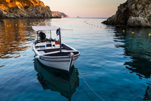 Barca ormeggiata in mare vicino alla costa rocciosa riflessa nell'acqua vacanze in grecia isola di corfù