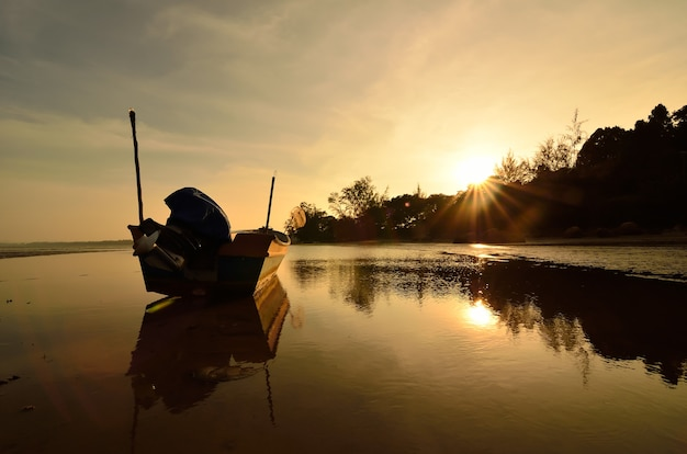 Barca vicino alla spiaggia quando il sole tramonta
