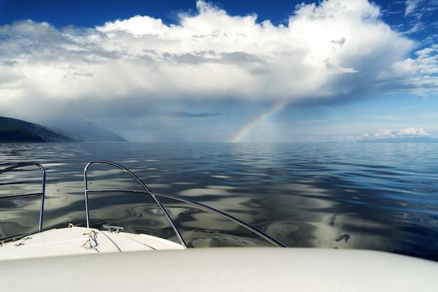 Barca in mare vicino alla costa nuvole bianche e arcobaleno