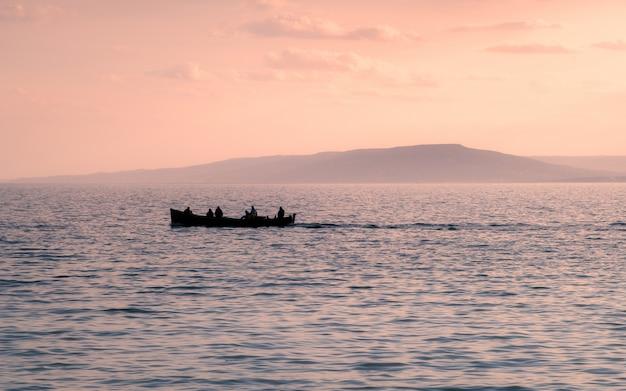 Sagoma di barca con uomo sull'acqua nel tramonto con la montagna.
