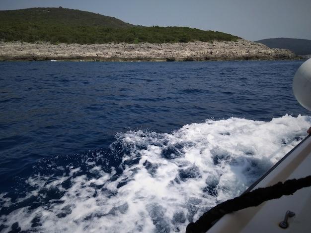 Viaggio in barca. vista dal ponte di una barca in viaggio. vista di barche e montagne. le onde stanno arrivando.