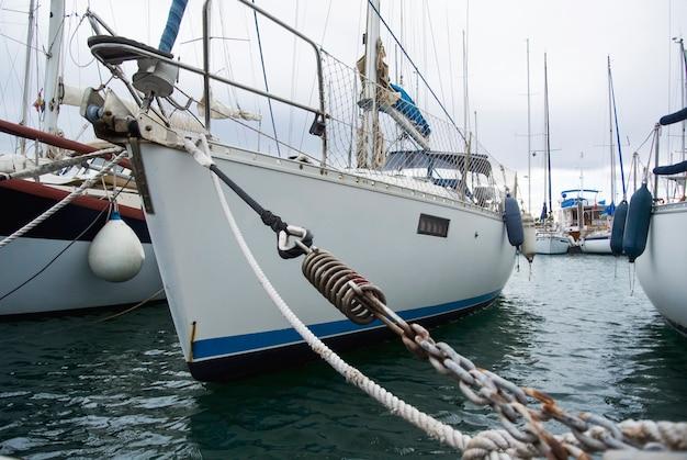 Barca nel porto di valencia nel mar mediterraneo. riflessione nell'acqua. l'yacht bianco è nel porto spagnolo di valencia all'inizio della primavera. cielo nuvoloso.