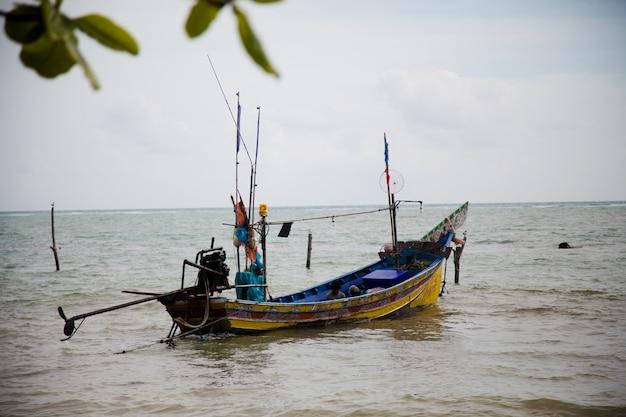 Una barca con pescatori in riva al mare in thailandia