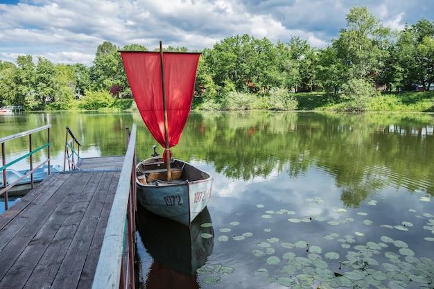 Una barca con una vela scarlatta sul lago