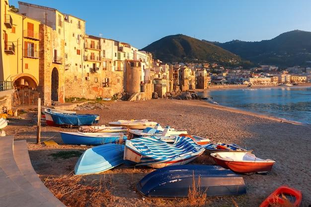 Barche sulla spiaggia e case soleggiate nella città costiera cefalù al tramonto, sicilia, italy