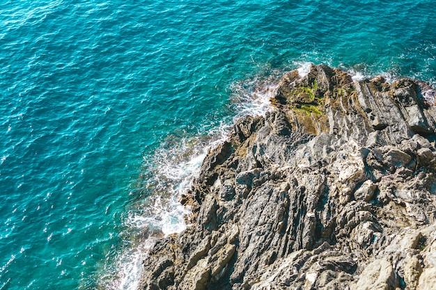 Barche su acqua blu vicino alla spiaggia nel parco nazionale di cinque terre in italia