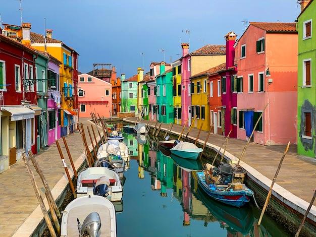 Attracco barche e case colorate in una strada del canale case sull'isola di burano, venezia, una gente irriconoscibile sullo sfondo.