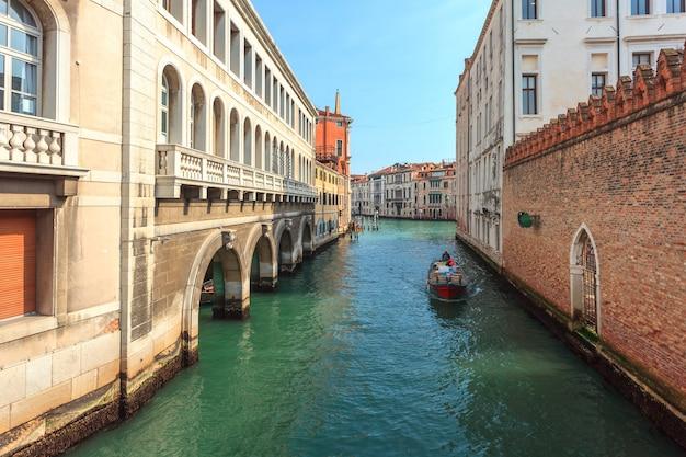 Barche sul canale stretto tra case storiche colorate a venezia.