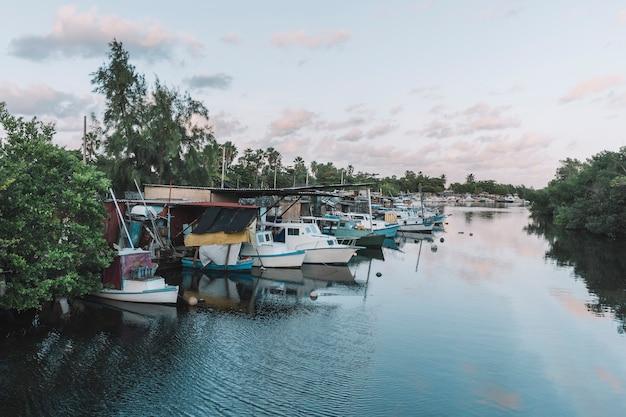 Parcheggio barche in acqua. barche ormeggiate nel fiume sotto il cielo azzurro e nuvoloso in estate.