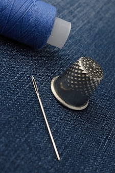 Una bobina di filo con un ago e un ditale. su sfondo denim. avvicinamento.