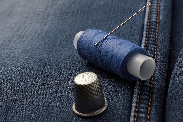 Una bobina di filo con un ago e un ditale