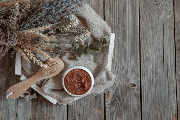 Spazzola per il corpo, scrub naturale e un bouquet di erbe di campo su una superficie di legno.