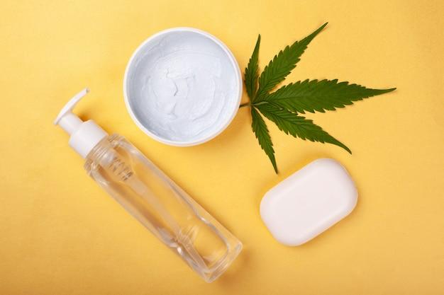 Cura del corpo, cosmetici alla cannabis su uno sfondo giallo.