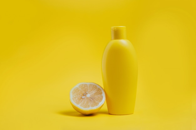 Prodotto per la cura del corpo e limone su giallo