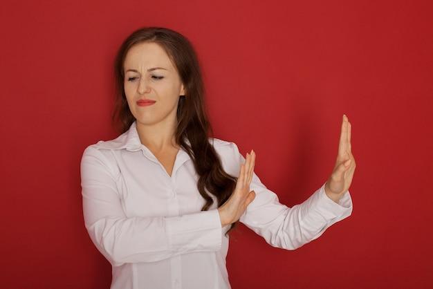 Linguaggio del corpo. bella giovane donna arrabbiata agitata disgustata che posa alla parete dello studio