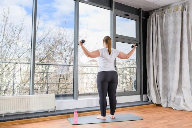 La donna paffuta positiva per il corpo resta indietro in leggings neri e alza le mani con i manubri dei pesi a piedi nudi sul tappetino