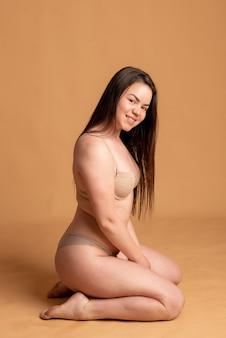 Corpo positivo. una ragazza in biancheria intima beige posa su uno sfondo rosa. foto di alta qualità