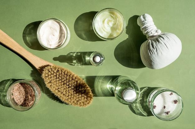 Trattamento corpo e spa concept maschera scrub crema e cosmetici a base di olio naturale su sfondo verde cellul...
