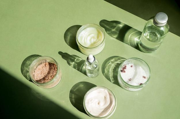 Trattamento corpo e spa concept maschera scrub crema e cosmetici con olio naturale su sfondo verde womans...