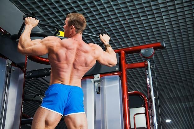 Bodybuilder facendo pull-up in palestra moderna. il giovane sportivo si tira su sulla barra. il mento dell'atleta al club sportivo. primo piano, copia dello spazio
