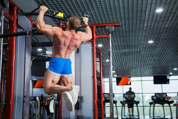 Bodybuilder facendo pull-up in palestra moderna. il giovane sportivo si tira su sulla barra. il mento dell'atleta al club sportivo. copia spazio