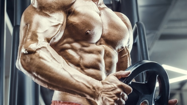 Culturista bello forte atletico uomo ruvido pompare i muscoli allenamento fitness e bodybuilding sano concetto di fondo -