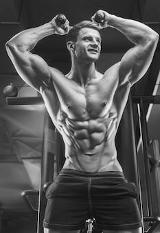 Culturista bello forte atletico uomo ruvido pompando tricipiti muscoli allenamento fitness e concetto di bodybuilding