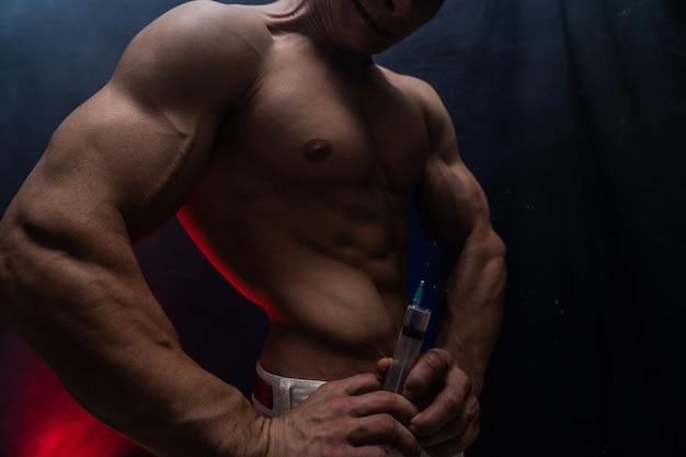 Culturista che tiene in mano un grande concetto di siringa di steroidi nello sport e nella dipendenza