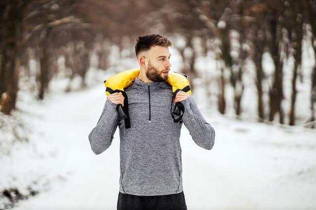 Culturista che tiene i pesi mentre si sta in piedi nei boschi al giorno d'inverno nevoso. bodybuilding, fitness invernale