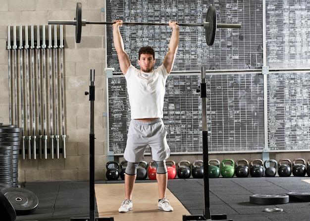Bodybuilder sollevamento bilanciere sopra la testa