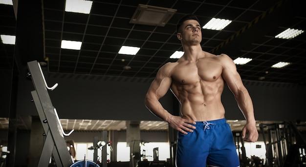 Uomo del bodybuilder con addominali perfetti, spalle, bicipiti, tricipiti e petto, personal trainer che flette i muscoli