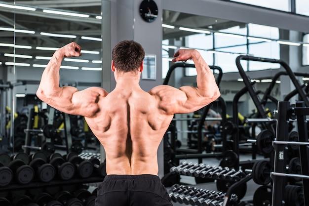 Uomo del bodybuilder con bicipiti, tricipiti e petto perfetti in palestra