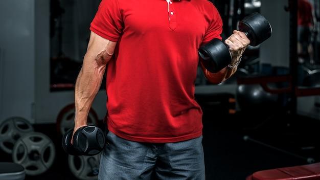 Bodybuilder in allenamento polo rosso con manubri