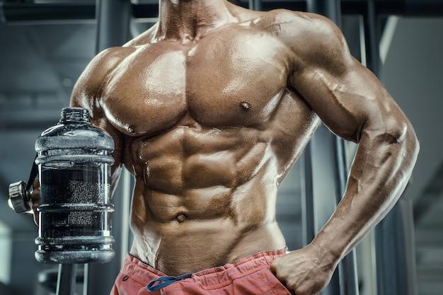 Bodybuilder forte atletico uomo ruvido acqua potabile dopo allenamento allenamento fitness e bodybuilding sano concetto