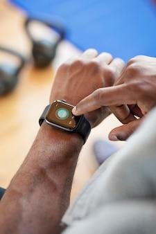 Bodybuilder che utilizza uno smartwatch in palestra