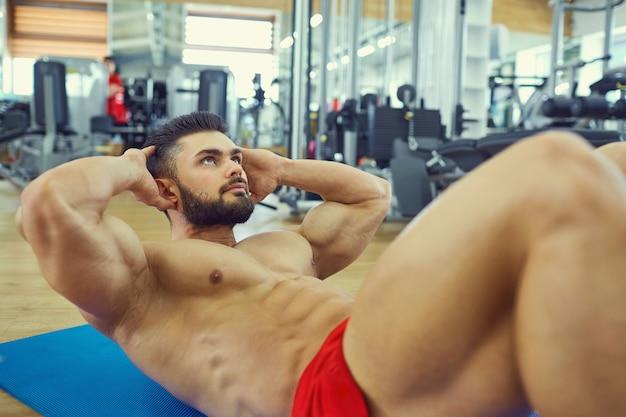 Bodybuilder con la barba fa esercizi addominali sul pavimento in palestra.